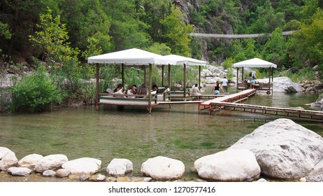 Goynuk, Turkey - August 5, 2014: Tourists, resting in the shade of arbors, located on the water in the canyon