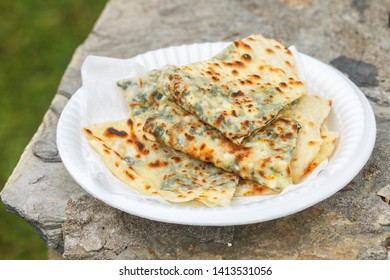 Gozleme. A traditional dish of Turkish cuisine in the form of flatbread stuffed with greens and cheese, wrapped inside. Baked in a pan called a saj. Selective focus