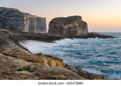 Gozo Island cliffs with Fungus Rock (small islet) during the spring storm. Dwejra, Maltese archipelago