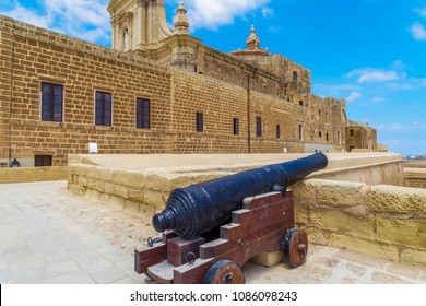 Gozo island, Malta Citadel fortified town canon. Old black canon on wooden stand at Saint John Bastion inside Cittadella - Castello acropolis in Victoria Town, part of UNESCO World Heritage Sites.
