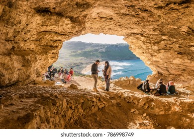Gozo island Malta December 2017, View of Ramla Bay, from inside Tal Mixta Cave Gozo ,people picnic in the cave