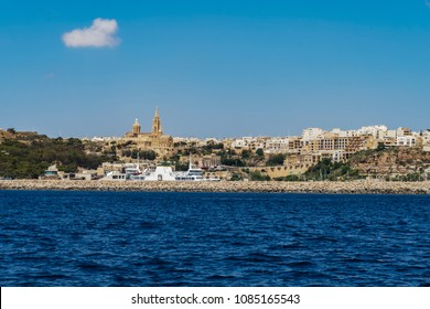 Gozo Island, Malta Gozo port landscape. Gozo Channel Line Ferry at port with background view of city buildings and Ghajnsielem Parish Church.