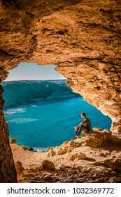 Gozo island Malta, young man and a View of Ramla Bay Malta, from inside Tal Mixta Cave Gozo