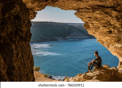 Gozo island Malta, young man and a View of Ramla Bay, from inside Tal Mixta Cave Gozo