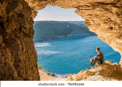 Gozo island Malta, young man and a View of Ramla Bay, from inside Tal Mixta Cave Gozo looking out over the blue ocean on a bright day