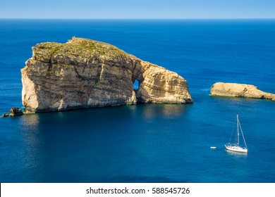 Gozo, Malta - The amazing Fungus Rock at Dwejra bay with sailboat, blue sea water and sky on a beautiful summer day