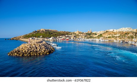 Gozo, Malta - The ancient port of Mgarr with lighthouse on the island of Gozo on a bright sunny summer day with blue sea water and clear sky