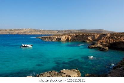 Gozo,Comino island,Maltese coastline with the cliffs,gold rocks over the sea in Malta island with the one yacht in the backround. Malta,Malta view,holiday destination,Maltese maltese coastline