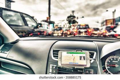 GPS device in a car, satellite navigation system along city streets.
