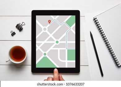 GPS map navigation app on tablet screen with office objects on white wooden table. Location tracker concept. Flat lay
