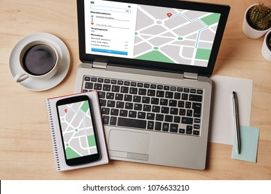 GPS map navigation app on laptop and smartphone screen over wooden table. Location tracker concept. Flat lay