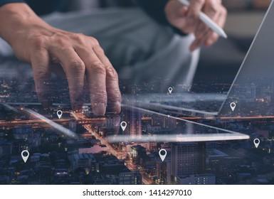 GPS-Karte, Pin-Adresse-Position auf mobilen Apps. Doppelte Belichtung von Hand mit digitalen Tablet-Suche Zielort in der Nachtstadt während der Arbeit mit Laptop-Computer.