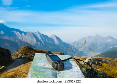 GPS navigator and map on Alps mountain background