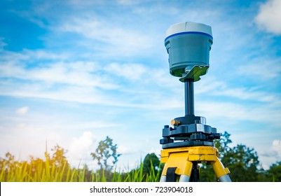 GPS surveying equipment on blue sky and white clouds background. GPS, GIS, and GNSS equipment. Land survey for map. Technology for marks land to made satellite map on the earth. Smart GNSS/GPS survey.