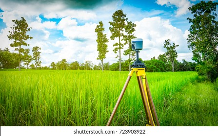 GPS surveying instrument install on tripod in green rice field, Thailand with beautiful sky and cumulus clouds