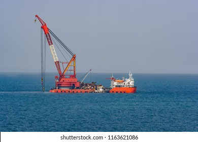 Grab dredegr ship cleaning sea bottom from metal scrap and garbage.