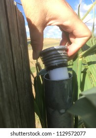 Grabbing a geo cache container from the fence