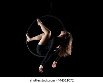 Graceful aerial dancer woman doing her performance with a hoop isolated on black