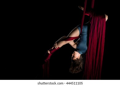 Graceful aerial dancer woman doing her performance isolated on black