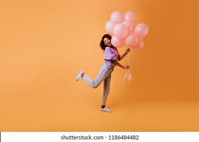 Graceful african female model in casual clothes fooling around on yellow background. Indoor photo of emotional birthday girl dancing with party balloons.