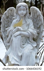 A graceful angel of stone watches over the gardens.