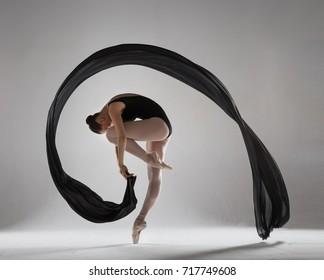 Graceful ballerina with a black veil. Studio photography.