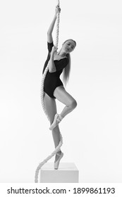 graceful ballerina in pointe shoes is posing with rope on white studio background. Black and white photo.