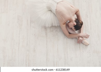 Graceful Ballerina stretching, ballet background, top view on white wood floor
