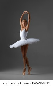 graceful ballerina in white tutu and pointe shoes dancing on gray background