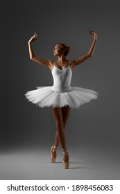 graceful ballerina in white tutu is standing on pointe in an elegant pose on gray background