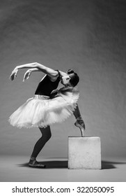 Graceful ballerina in white tutu standing on toes. Studio shot, grayscale image.