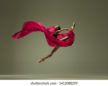 Graceful ballet dancer or classic ballerina dancing isolated on grey studio background. Woman with the pink silk cloth. The dance, grace, artist, contemporary, movement, action and motion concept. - Shutterstock ID 1412088299