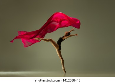 Graceful ballet dancer or classic ballerina dancing isolated on grey studio background. Woman with the pink silk cloth. The dance, grace, artist, contemporary, movement, action, motion concept.