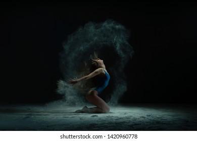 Graceful barefoot woman dancing in cloud of dust
