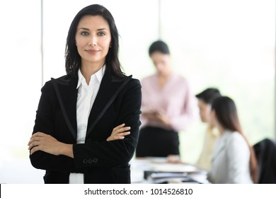 Graceful and beautiful business woman in black suit standing with dignified manner in office, group of young business team in background