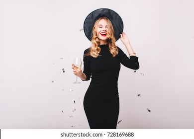 Graceful blonde girl in black dress and hat dancing under confetti and laughing. Indoor portrait of cute young witch drinking wine with pleasure at halloween party.