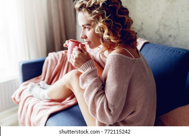 Graceful blonde woman enjoying smell of cappuccino  , dreaming and looking into the window.  Wearing pink knitted sweater.