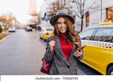 Graceful brunette woman in vintage coat walking down the street with phone in hand. Outdoor portrait of smiling refined girl in hat an red sweater standing next to yellow taxi.