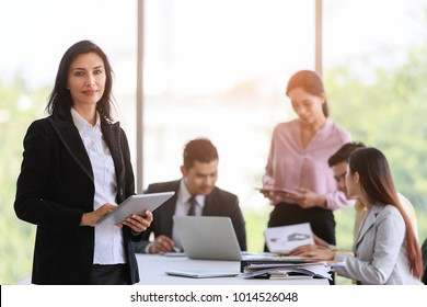 Graceful business woman in black suit standing with dignified manner in office, group of young business team in background