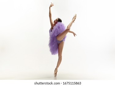 Graceful classic ballerina dancing, posing isolated on white studio background. Bright purple tutu. The grace, artist, movement, action and motion concept. Looks weightless, flexible. Fashion, style.