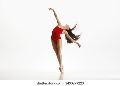 Graceful classic ballet dancer or ballerina dancing isolated on white studio background. Woman in bright red clothes like a combination of wine and milk. The grace, artist, movement, action and motion