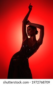 Graceful fashion model girl poses at studio in elegant sparkling dress in red light. Beautiful dancing girl. Beauty, fashion.