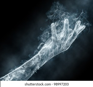 Graceful female hand from a smoke on a black background. Mysterious and magic art