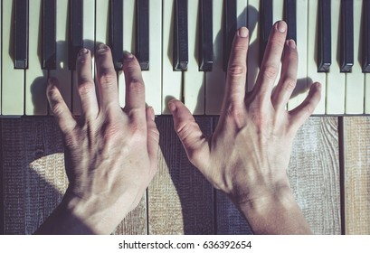 Graceful female hands playing old piano. Close up. Vintage toning. Top view