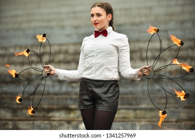 Graceful girl dancing passionate dance with fire fan in his hand. Dancer in white blouse. Fire show. Rezekne - Latvia, March 2019