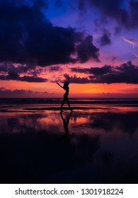 Graceful girl dancing at sunset. Reflection on the water. Indonesia, Bali Island