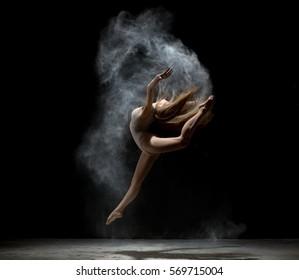 Graceful girl dancing in white dust powder