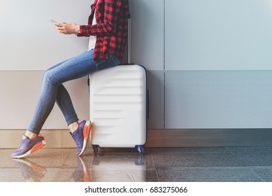 Graceful girl is using mobile phone in modern terminal