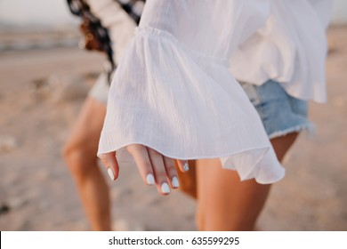 Graceful girl in vintage blouse and denim shorts with trendy white manicure having fun outside running on the sand. Couple spending time together dancing in desert. Body part, blur background, outfit