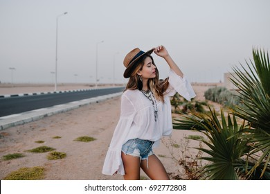 Graceful girl wearing white blouse and trendy hat posing with eyes closed next to exotic plant in front of highway. Beautiful young woman standing with hand up on the sand near to road enjoys evening